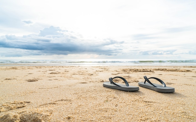 Sandales sur la côte de mer sablonneuse