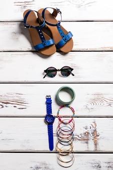 Sandales femme et petits accessoires. chaussures et accessoires sur étagère. chaussures femme pour l'été. de petits accessoires sympas.
