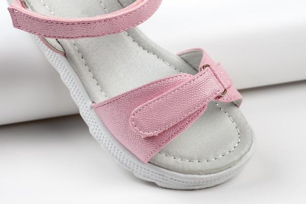 Sandales isolées roses sandales roses pour enfants à semelles blanches et fermetures velcro isolées sur un...