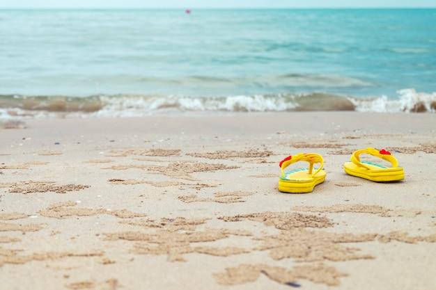 Sandales jaunes sur la plage.