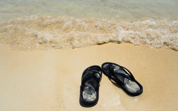 Sandales noires sur la plage de sable et les vagues de la mer. vacances d'été ensoleillées ma