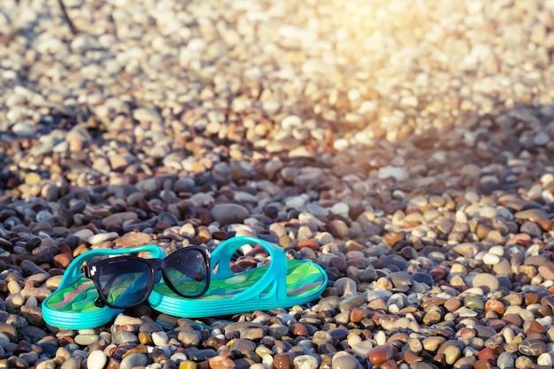 Sandales de plage bleues et lunettes de soleil sur les pierres du bord de mer