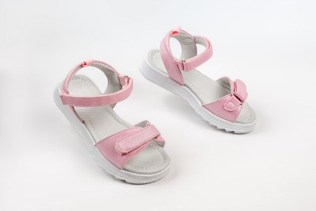 Sandales pour enfants roses en cuir brillant avec fermetures velcro semelles blanches plates isolées sur un fond blanc...