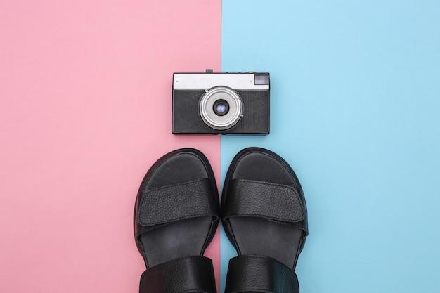 Sandales pour femmes en cuir noir et appareil photo sur fond pastel bleu rose. vue de dessus. mise à plat