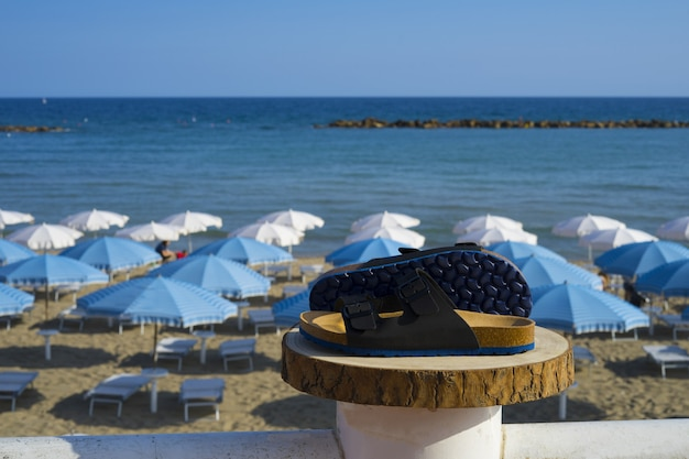 Sandales pour hommes exposées sur un podium en bois avec panorama sur la plage en été