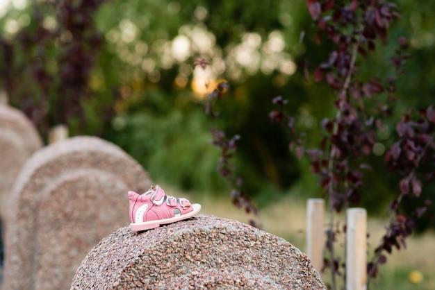 Sandales roses pour enfants sur fond d'arbres verts dans le parc du soir