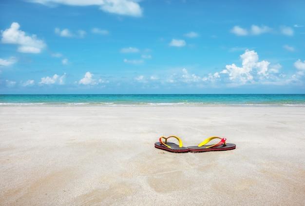 Sandales sur sable propre et eaux turquoises.