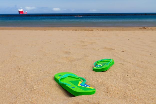 Sandales vertes laissées sur le chemin de l'eau sur la plage de sable