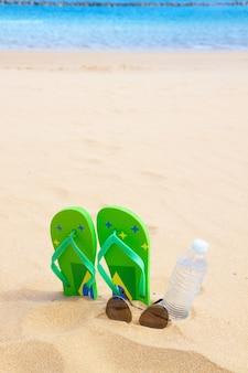 Sandales vertes sur la plage de sable avec une bouteille d'eau claire et des verres