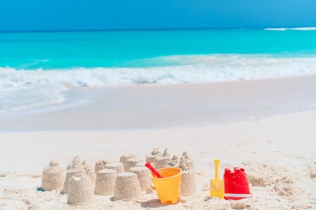 Sandcastle à la plage blanche avec des jouets en plastique et vue sur la mer