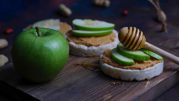 Sandwich au beurre de cacahuète naturel croquant avec du pain de gâteau de riz et des tranches de pomme verte et du miel.