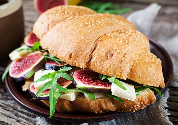 Sandwich au croissant frais avec roquette au fromage brie et figues. délicieux petit déjeuner. nourriture savoureuse.