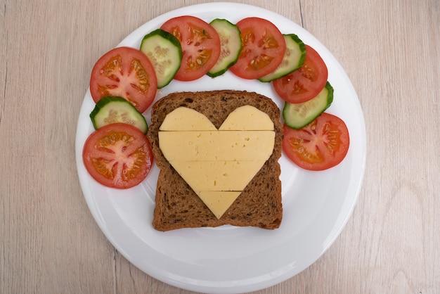 Sandwich au fromage en forme de coeur avec des légumes sur une plaque blanche.
