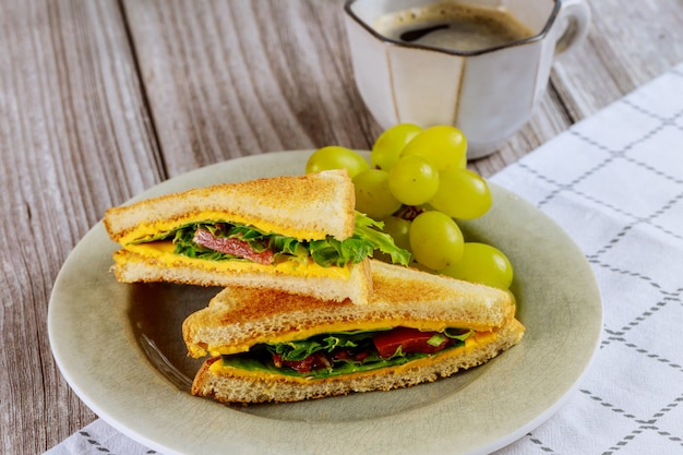 Sandwich au fromage grillé maison, raisin et café pour le petit déjeuner.