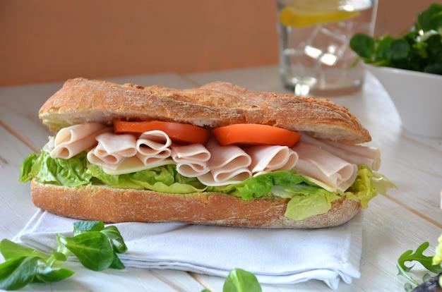 Sandwich au fromage et jambon de dinde servi avec laitue et tomate