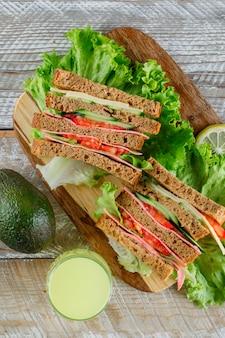 Sandwich au fromage, jambon, jus, avocat à plat sur planche de bois et à découper