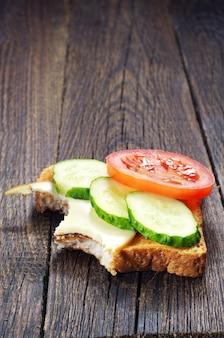 Sandwich au fromage et légumes qui a été mordu sur une table en bois