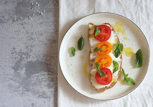 Sandwich au fromage, tomates et basilic sur une assiette à dessert. le dessus du sandwich est arrosé de beurre. vue de dessus