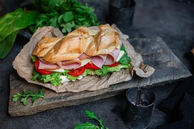 Sandwich au jambon fromage tomate et laitue sur fond sombre