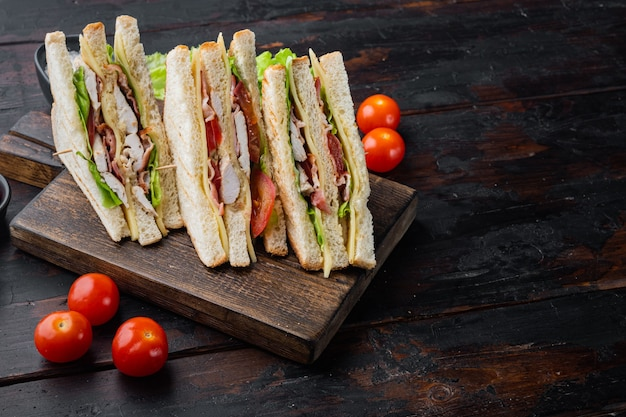 Sandwich au jambon, fromage, tomates, laitue, viande de poulet et pain grillé, sur la vieille table en bois avec copie espace pour le texte