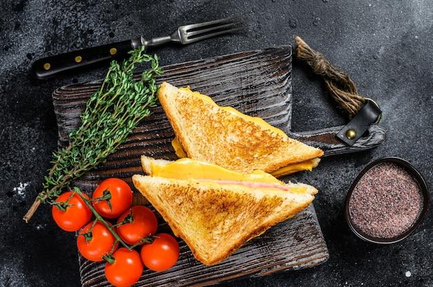 Sandwich au jambon grillé et fromage sur une planche à découper