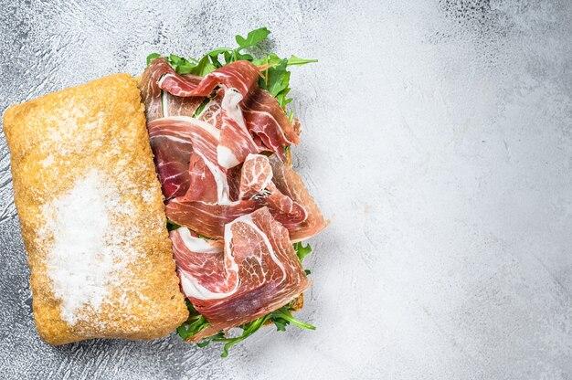 Sandwich au jambon de parme prosciutto sur pain ciabatta avec roquette. fond blanc. vue de dessus. espace de copie.