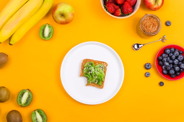 Sandwich au kiwi et beurre d'arachide sur jaune.