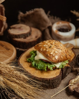 Sandwich au pain avec du fromage fondu et de la laitue sur un morceau de bois.