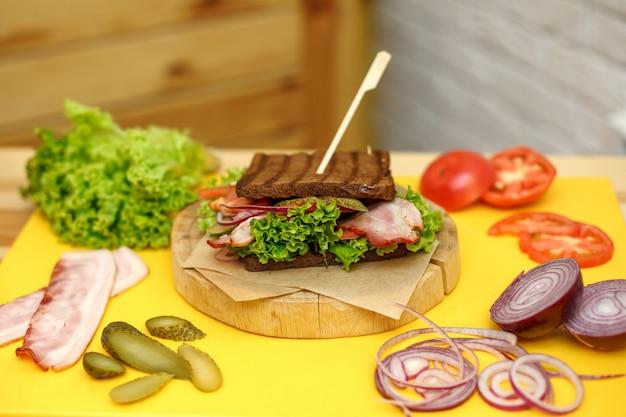 Sandwich au pain noir grillé sur une plaque en bois sur un plateau jaune
