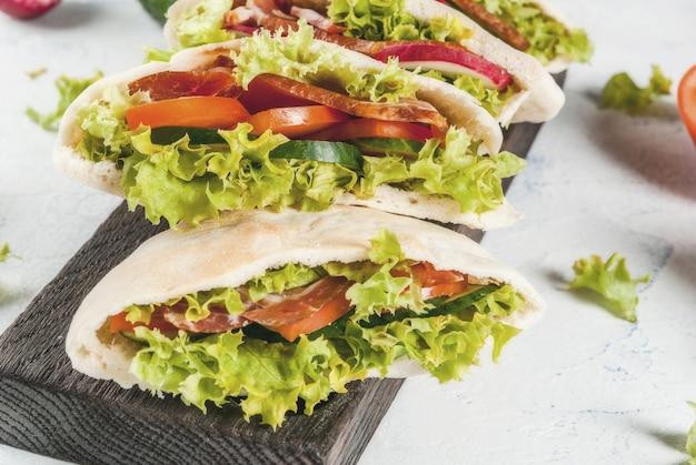 Sandwich au pain pita avec des légumes frais sur une table en béton léger