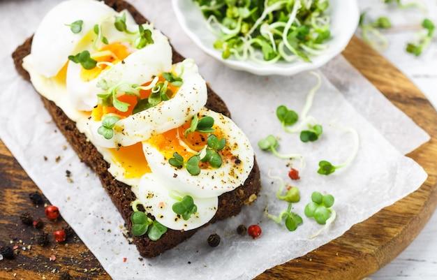 Sandwich au pain de seigle avec œuf à la coque, fromage, poivre fraîchement moulu et germes de daikon ou de radis,