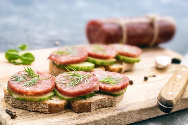 Sandwich au pain de seigle avec saucisse fumée, aneth et concombre sur planche à découper en gros plan