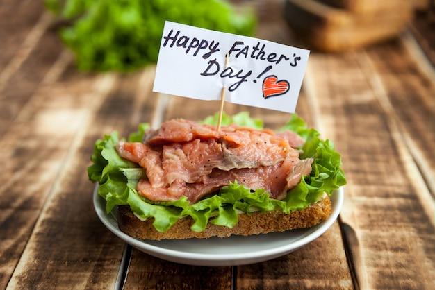 Sandwich au poisson rouge sur pain de seigle avec une feuille de laitue avec félicitations pour la fête des pères