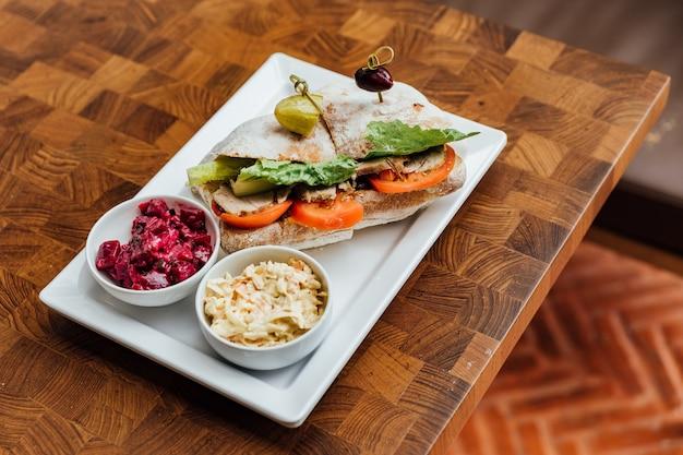 Sandwich au poulet grillé à base de pain, tomates et laitue servi avec salade de betteraves