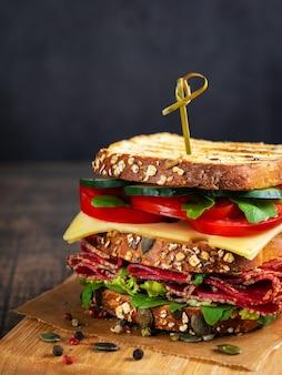 Sandwich au salami, fromage et légumes frais sur une planche à découper en bois rustique