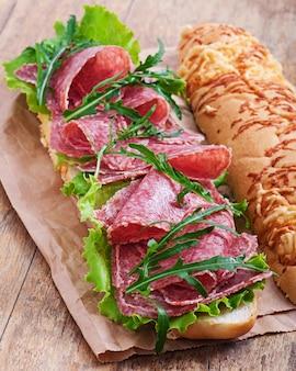 Sandwich au salami, laitue, tomate et roquette