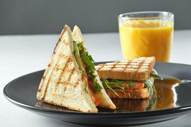 Sandwich au saumon avec du jus d'aliments sains sur une table