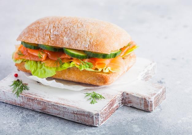 Sandwich au saumon frais et sain avec de la laitue et du concombre sur une planche à découper vintage sur fond de pierre blanche. collation du petit déjeuner