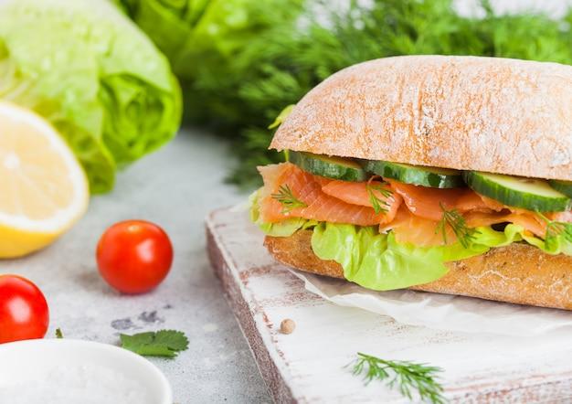 Sandwich au saumon frais et sain avec de la laitue et du concombre sur une planche à découper vintage sur fond de pierre. collation du petit déjeuner. tomates fraîches, aneth et citron.