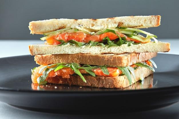 Sandwich au saumon fumé sur seigle à la roquette, fromage à la crème sur l'assiette