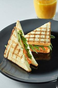 Sandwich au saumon grillé avec du jus sur une table