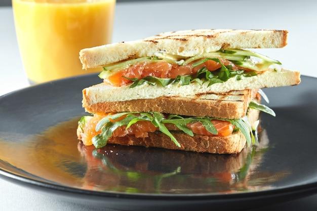 Sandwich au saumon pour le petit déjeuner avec du jus d'orange