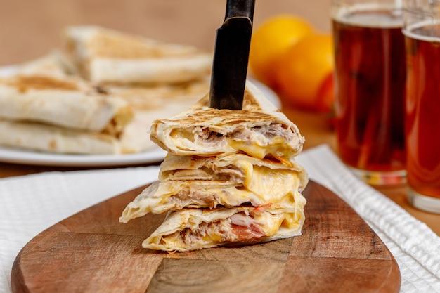 Sandwich au shawarma de restauration rapide avec thon, tomates et fromage.