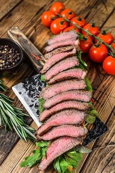 Sandwich au steak grillé avec roquette et fromage sur un ceaver de viande. fond en bois. vue de dessus.
