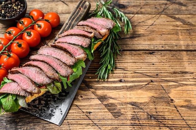 Sandwich au steak grillé avec roquette et fromage sur un ceaver de viande.