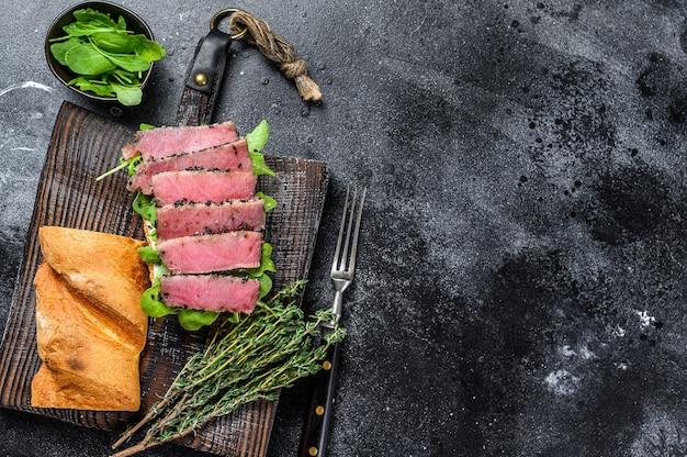 Sandwich au steak de thon baguette avec roquette sur une planche à découper