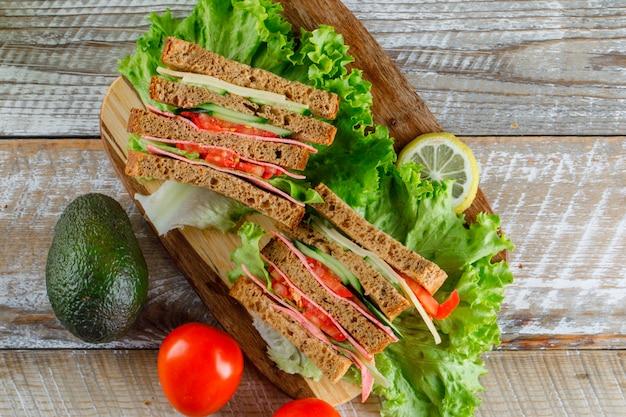 Sandwich aux légumes avec fromage, jambon, citron, avocat sur planche de bois et à découper, pose à plat.