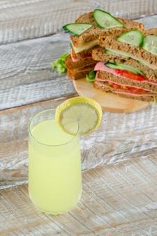 Sandwich aux légumes avec fromage, jambon, limonade sur planche de bois et à découper, vue grand angle.