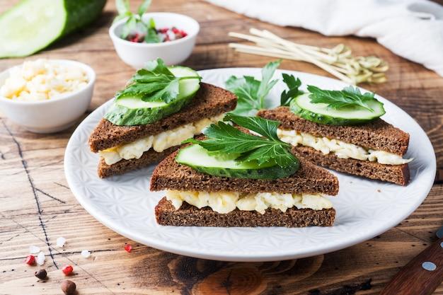 Sandwich aux oeufs brouillés, concombres et persil sur fond rustique en bois.