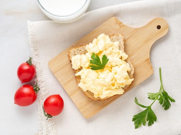 Sandwich aux œufs brouillés poêlés sur une planche à découper en bois, vue de dessus.